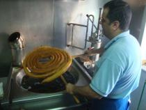 The churrero proudly displays the churro coil fresh from the deep frier